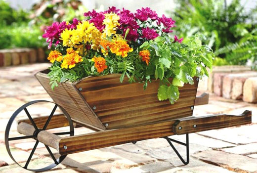 Вазоны с цветами в деревянной тачке