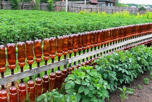 Ограждение в огороде из пластиковых бутылок